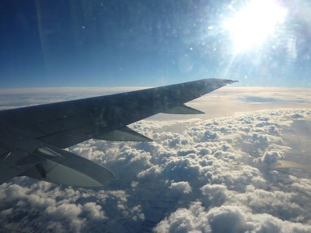 Uitzicht vanuit het vliegtuig op het wolkendek met een heldere zon