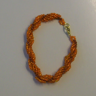 A bracelet of beaded spiral rope in orange colors