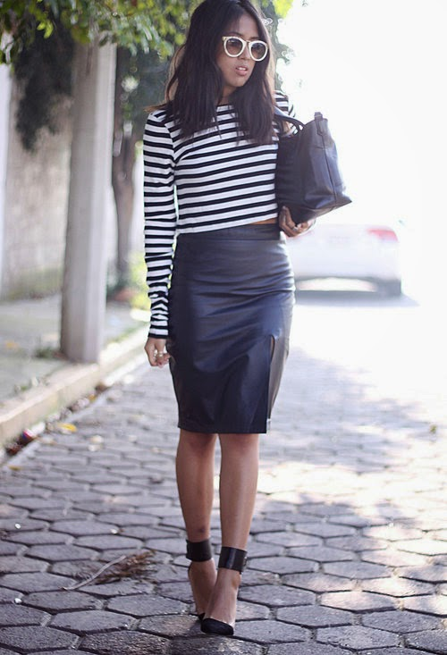 She is wearing a white stripe crop top and leather midi skirt