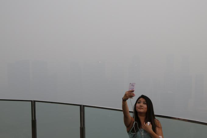 A woman takes a selfie with the skyline of the central business district shrouded by haze in Singapore on 14 September 2015.