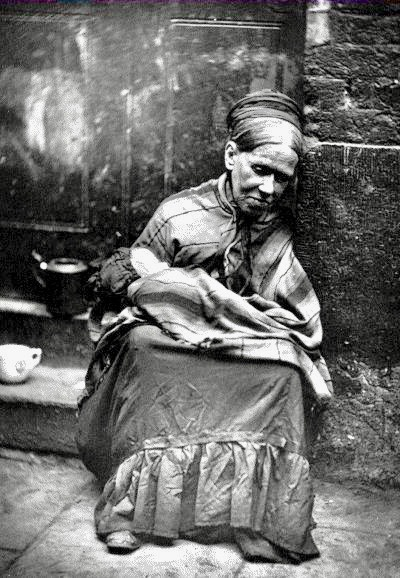 Victorian era poverty. Woman sits on the curb holding an infant. Speak Your Mind and other stories of Grandmas and reason. marchmatron.com
