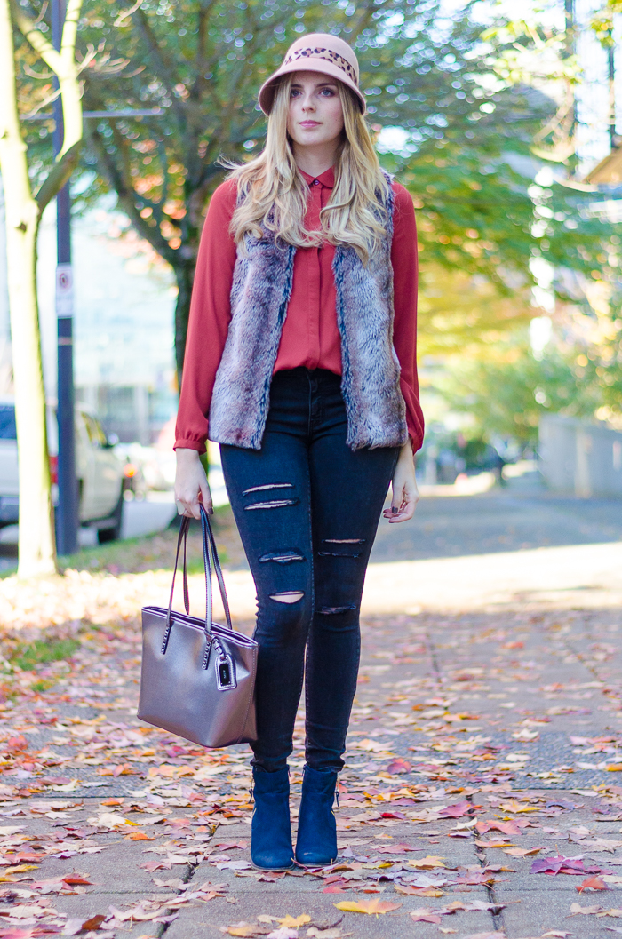 Casual American Eagle ripped denim jeans styled with retro inspired fur vest and metallic Aldo handbag