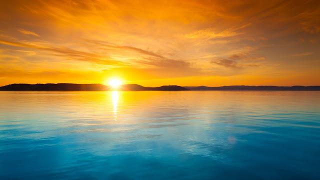 Zonsondergang boven het water. Het water is blauw en de lucht oranje.