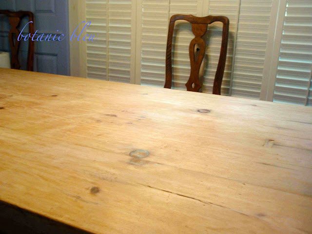 After scrapping wax, bleaching, and sanding a table made with reclaimed pine boards, character, distress, and deep scratches remained