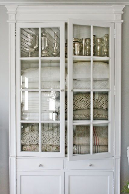 Painted vintage glass front cabinet filled with vintage linens - found on Hello Lovely Studio