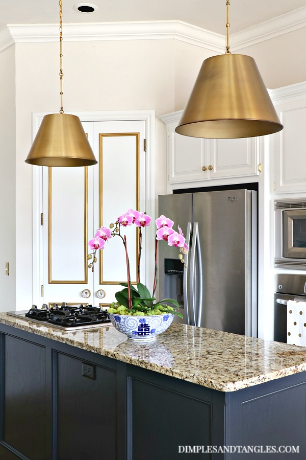 alden brass pendants, white doors with gold molding, black island