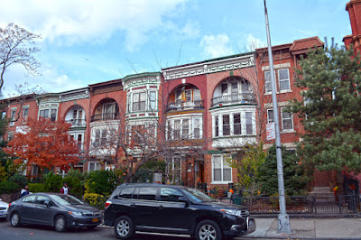Row of several similar red brick row houses with loggias