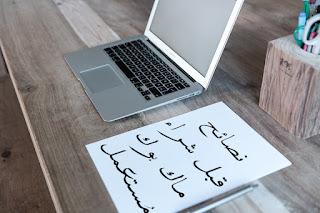 ورقة مكتوب عليها نصائح قبل شراء ماك بوك مستعمل بجانب جهاز ماك بوك برو من شركة آبل