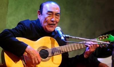 Foto de Oscar Avilés cantando con su guitarra
