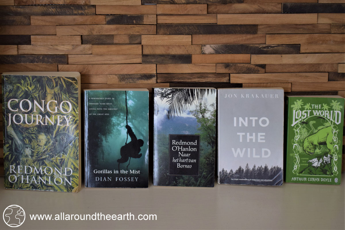 Five of the best travel and adventure inspiring books: Into the Wild by Jon Krakauer, Congo Journey and Into the Heart of Borneo by Redmond O'Hanlon, The Lost World by Arthur Conan Doyle, and Gorillas in the Mist by Dian Fossey