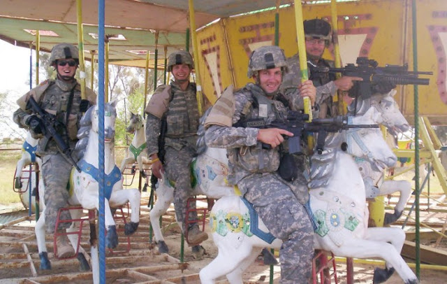 Jovenes soldados uniformados y armadados jugando en una calecita
