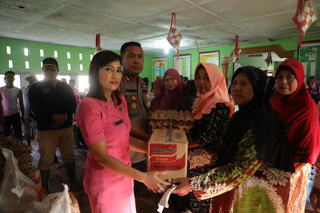 Kapolres Asahan AKBP Faisal Napitupulu dan Ketua Bhayangkari Cabang Asahan saat memberikan bantuan kepada korban banjir.