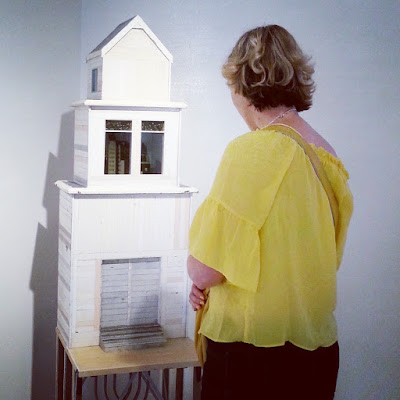 Woman standing in front of a miniature building in an art gallery.