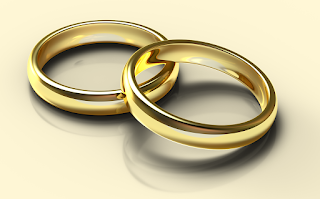 Computer generated image of two simple gold wedding bands, one lying partially atop the other