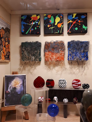 Corner of an art gallery with a variety of colourful tapestry, painted and glass art works on display.