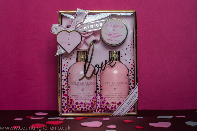 A box with 2 large pink bottles and tub and rose shaped body polisher