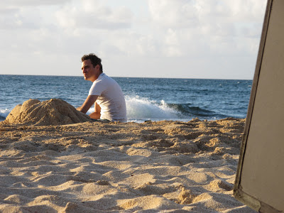 Joaquin Phoenix as Freddie Quell in The Master, sitting beside the sand sculpture of a woman, directed by Paul Thomas Anderson