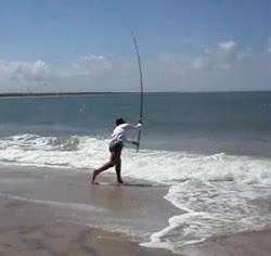 Foto de um pescador fazendo um arremesso com uma vara de pesca de praia