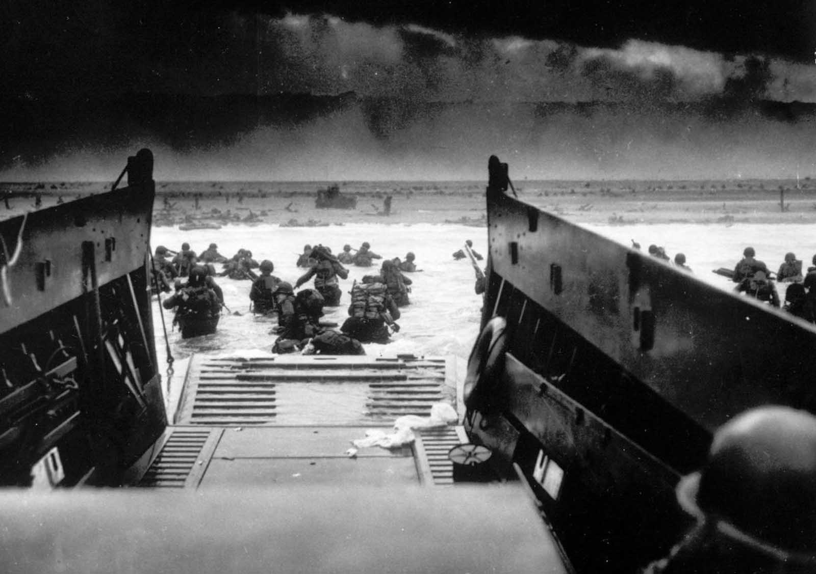 While under attack of heavy machine gun fire from the German coastal defense forces, American soldiers wade ashore off the ramp of a U.S. Coast Guard landing craft, during the Allied landing operations at Normandy, France on D-Day, June 6, 1944.