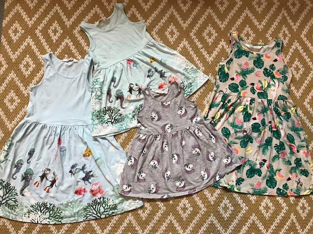 4 sleveless summer dresses on a rug, 2 under the sea pale blue ones in age 6 and 18 to 24 months, a 18-24 month grey one with white unicorn heads and a beige rainforest themes dress