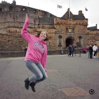 awayfromblue Instagram | tourist hoodie jumping pic at Edinburgh castle pink sweater grey jeans ankle boots