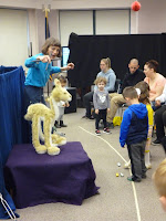 Woman holds marionette llama puppet on a small stage while, from the left a group of about six parents and children look on.