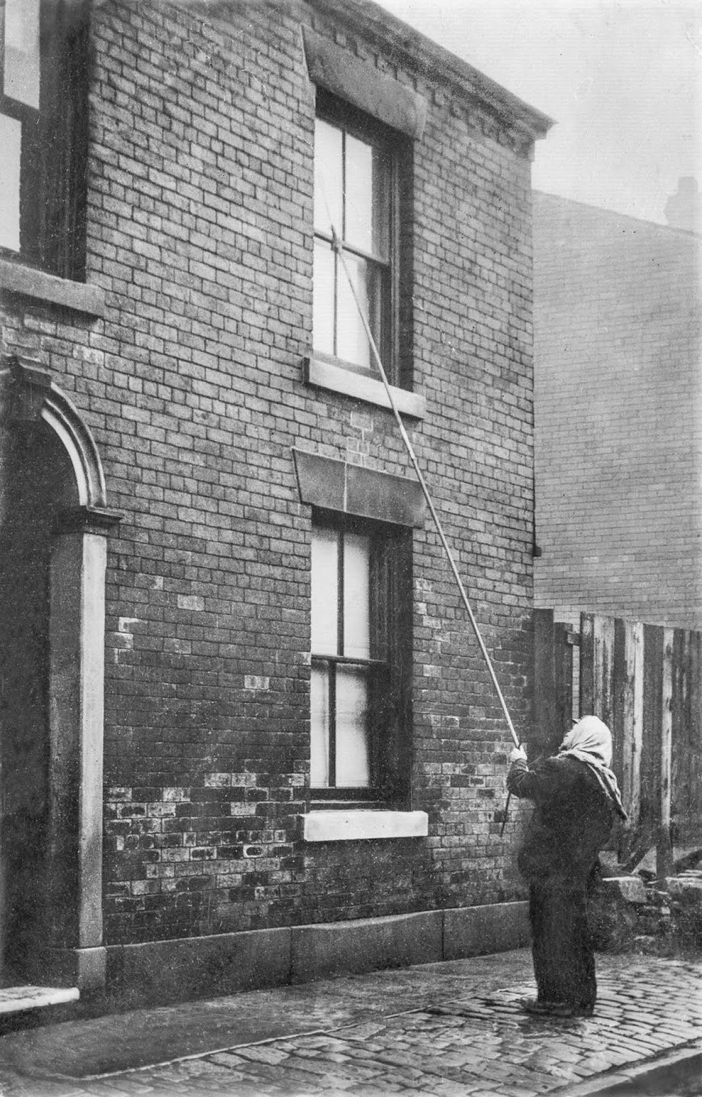 A knocker-up rouses a client in Lancashire. c. 1900.