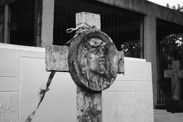 A cross on top of a tomb at La Loma Cemetery
