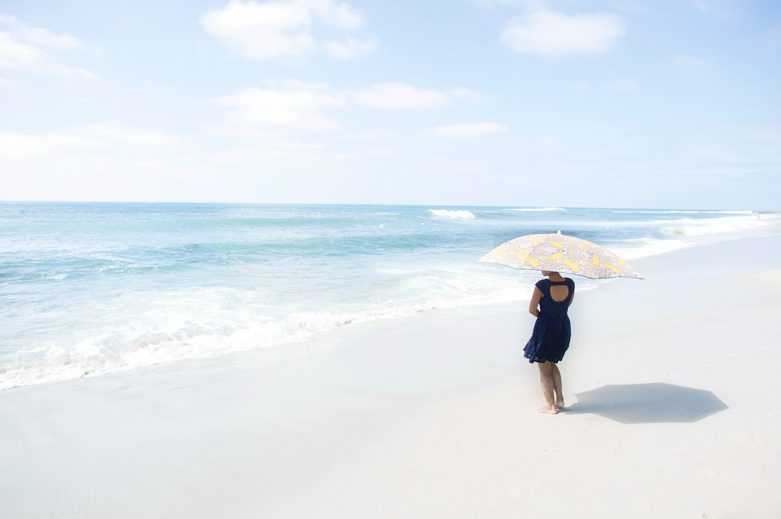 woman alone on a beach with a parasol staring out at a blue sea