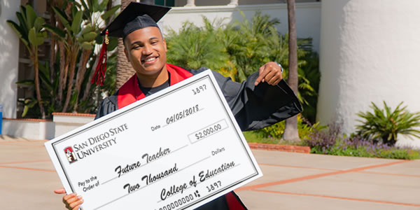 student holding scholarship check