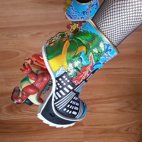 close up of dinosaur themed ankle boot on foot with speaker visible in platform