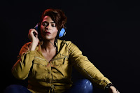 a woman holding a headphone and listening to music