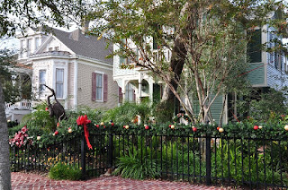 Victorian home decorated for Christmas with wood Egret sculpture in garden
