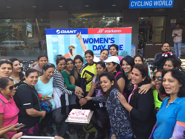 Women riders celebrating the women's day by cutting the cake