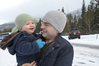 baby boy in yoda hat with his dad in the snow