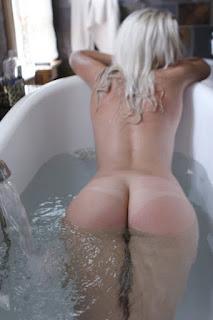 blonde nude escort in bath lying on her tummy