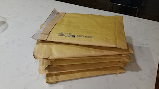 Pile of mailers containing proofs of the book And Yet We Rise for Beta Readers