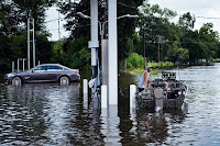 A man waits at a gas station with a boat while helping to evacuate a flooded neighborhood in Gonzales, Louisiana on August 16, 2016. (Credit: Brendan Smialowski/AFP/Getty Images) Click to Enlarge.