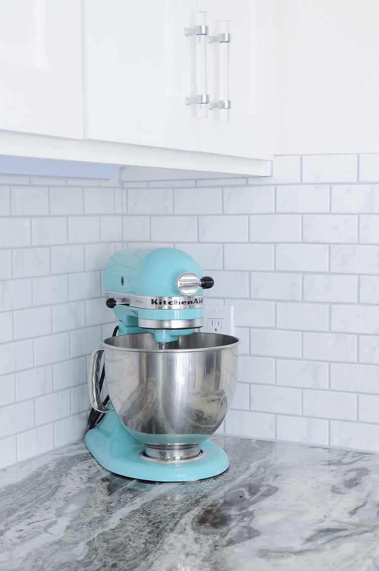 Martha Stewart blue Kitchenaid mixer in a bright white kitchen with marble backsplash.