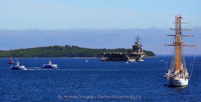 Halifax / Dartmouth Ferries cross the busy harbour with Esmerelda and the USS Dwight D Eisenhower at anchor.