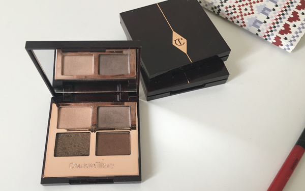 CHARLOTTE TILBURY COLOUR-CODED EYESHADOWS in The Golden Goddess with two closed Charlotte Tilbury Colour Coded Eyeshadows stacked adjacent on a dresser; the smashbox eyeshadow brush is visible in the bottom right corner
