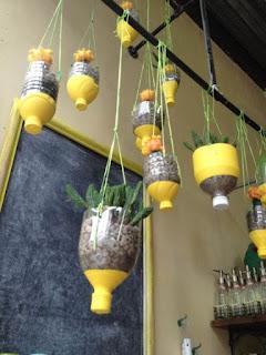 Maceteros ecológicos y colgantes con envases de leche para interiores