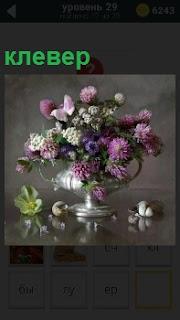 На столе стоит оригинальная красивая ваза с клевером внутри, листья упали на поверхность
