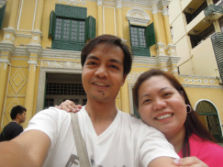A picture of a couple traveler and blogger in front of the Sto. Domingo Church in Macau