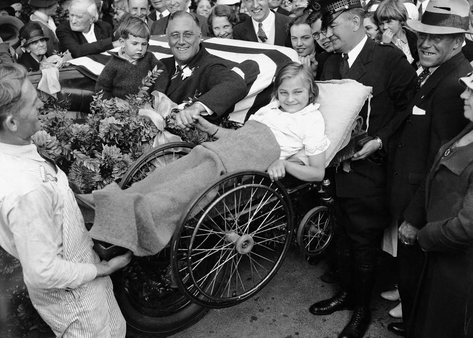 Franklin D. Roosevelt contracted polio in 1921 at age 39. Here, two men lift a little girl in a wheelchair so that Roosevelt can greet her from his vehicle during his first presidential campaign.
