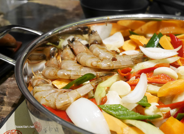 Vegetables and ingredients lined up inside the pot