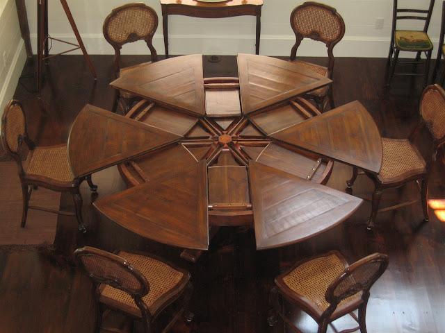 unique brown mahogany wooden dining room table with leaf in parts shape along with rattan wooden chairs on the wooden floor