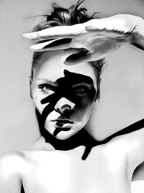retrato em preto e branco de uma mulher com sombras da mão