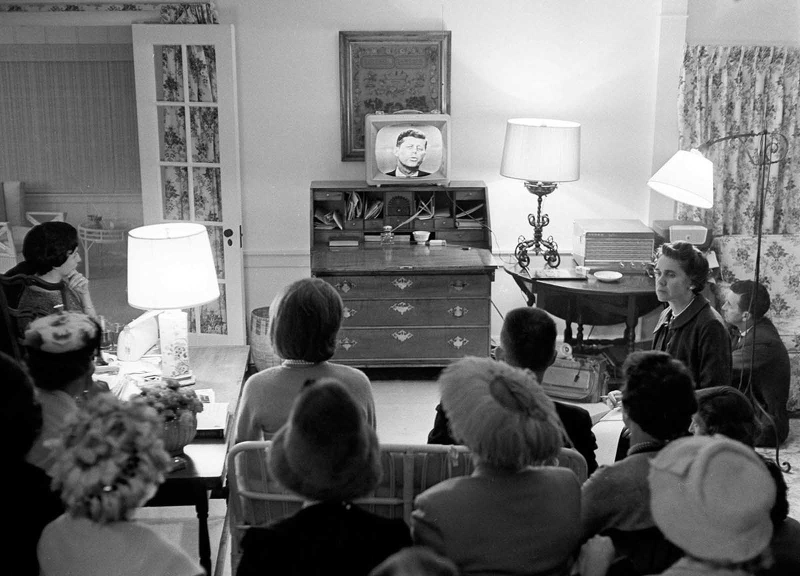 Jacqueline Kennedy, left center, sits in her living room with a group of Democrats watching her husband on television, debating domestic affairs with Vice President Richard Nixon, at her Hyannis Port, Massachusetts, home, on September 26, 1960.