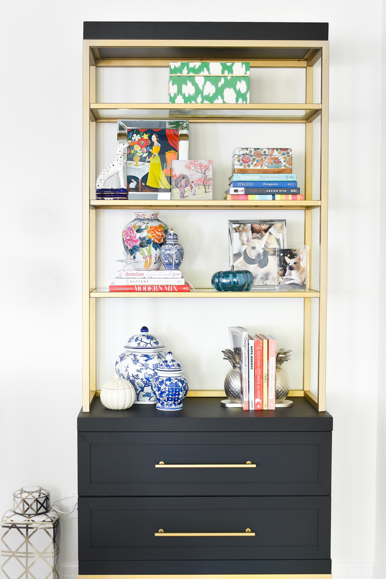 A black and gold bookcase styled to perfection with eclectic and colorful home decor accessories. #bookcase #bookshelf #interiorstylist